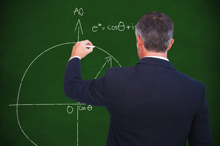 Rear view of businessman writing with chalk against black background
