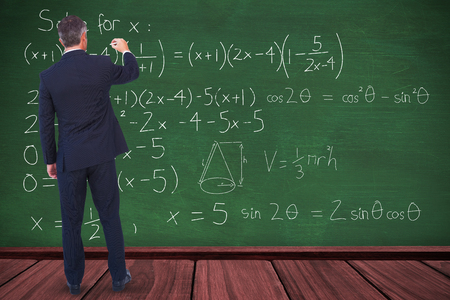 Businessman writing with chalk on white background against green room Stock Photo