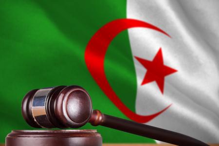 Hammer and gavel against 3d digitally generated algerian national flag