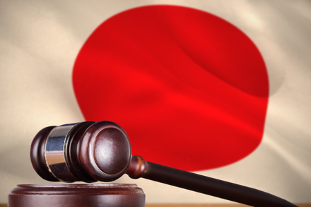Hammer and gavel against 3d digitally generated japanese national flag Stock Photo