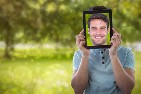 Man holding digital tablet in front of face against park Stock Photo