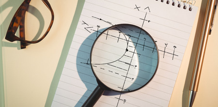Maths pattern against black background against magnifying glass on notepad amidst pen and eyeglasses Stock Photo