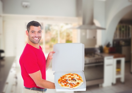 Digital composite of Happy deliveryman showing the pizza in the restaurant kitchen