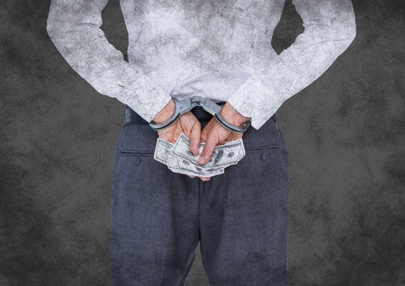 Digital composite of Back of business woman in handcuffs with money against grey grunge background