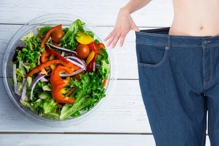 Digital composite of Composite image of midsection of woman measuring waist Standard-Bild