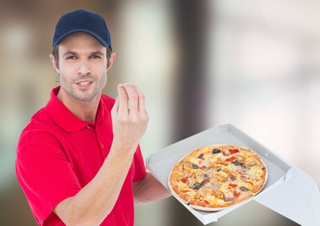 Digital composite of Deliveryman with pizza. Blurred background Stock Photo