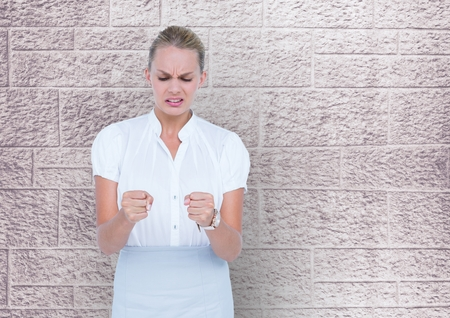 wrath: Digital composite of Business woman in front of a wall with look of disgust Stock Photo