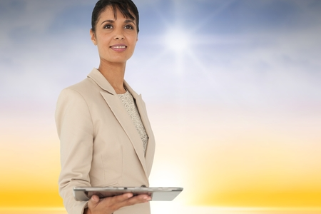 Digital composite of Composite image of woman using a tablet against sky background