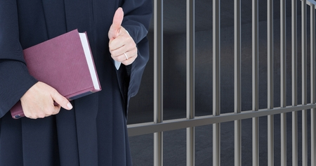interned: Digital composite of Judge holding book in front of prison bars cell