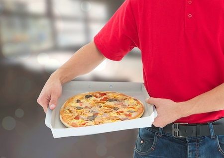 Digital composite of Deliveryman with pizza in the restaurant Stock Photo