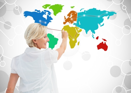 Digital composite of Older Woman drawing on Colorful Map with connected background