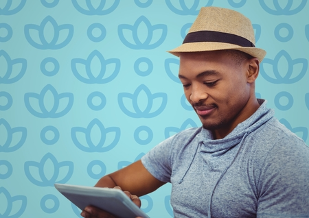 Digital composite of Man in fedora with tablet against blue floral pattern Stock Photo