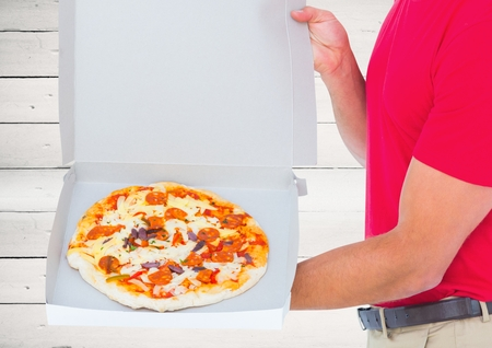Digital composite of Foreground of the pizza in the box with the deliveryman. wood background