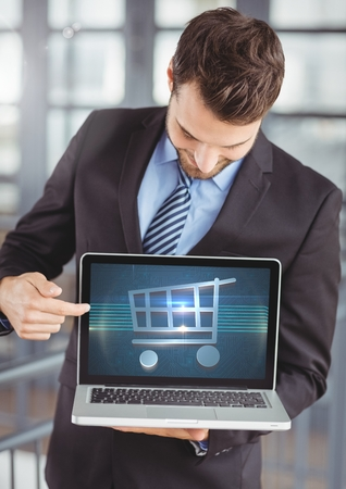 e commerce icon: Digital composite of Man using Laptop with Shopping trolley icon