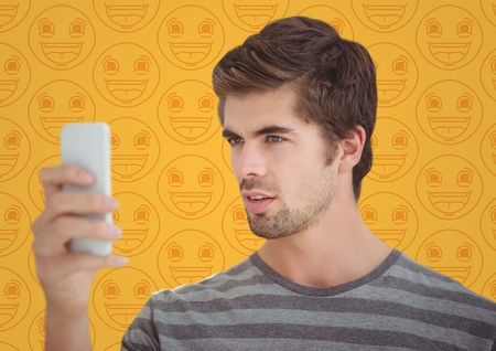 smilling: Digital composite of Man with phone against yellow emoji pattern