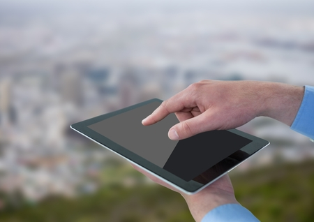tablet pc in hand: Digital composite of Hands with tablet against blurry skyline