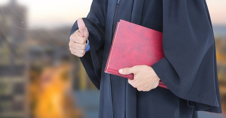 western script: Digital composite of Judge holding book in front of city Stock Photo