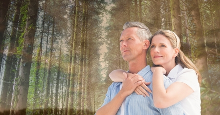 Digital composite of happy couple in front of trees