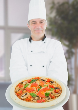 Digital composite of Chef with pizza in the restaurant. Blurred background