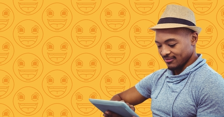 tablet pc in hand: Digital composite of Man in fedora with tablet against yellow emoji pattern
