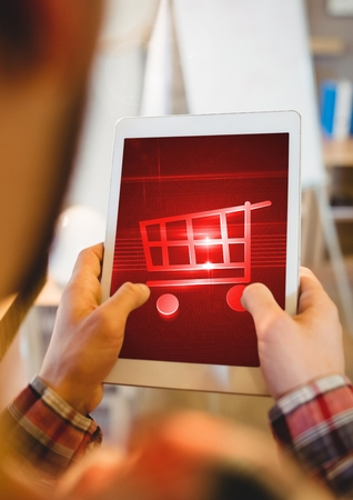 Digital composite of Person using Tablet with Shopping trolley icon Stock Photo