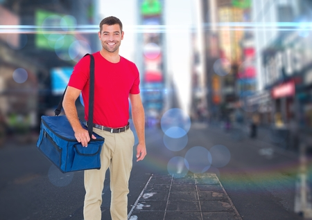 Digital composite of Happy pizza deliveryman with delivery bag in the city with lights Stock Photo