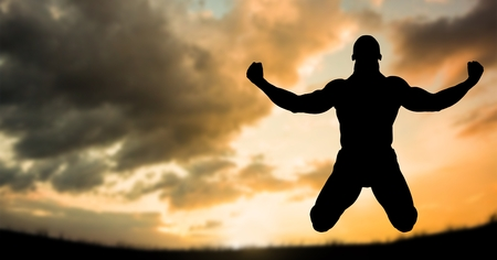 Digital composite of Silhouette muscular man in midair against sky during sunset Stock Photo