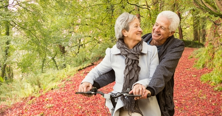 Digital composite of Loving senior couple riding bicycle in forest Stock Photo