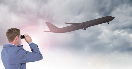 Digital composite of Businessman looking at airplane through binoculars