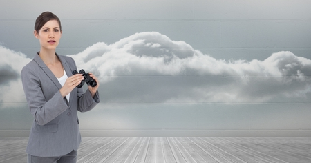 Digital composite of Portrait of businesswoman holding binoculars against sky