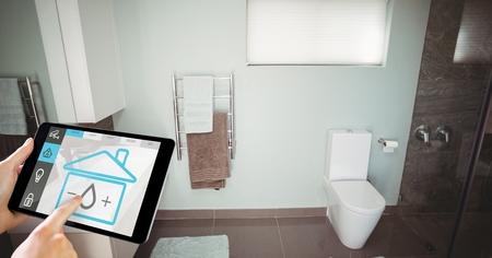 Digital composite of Hand using smart home application on digital tablet in washroom