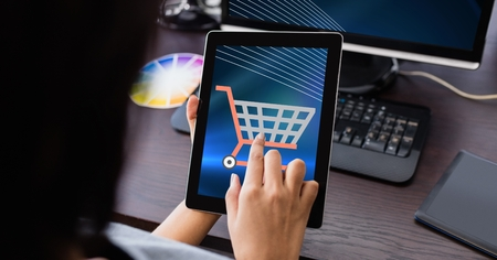 white wave: Digital composite of Hand touching shopping cart icon on tablet PC Stock Photo