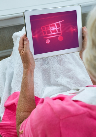 e commerce icon: Digital composite of Person using Tablet with Shopping trolley icon Stock Photo