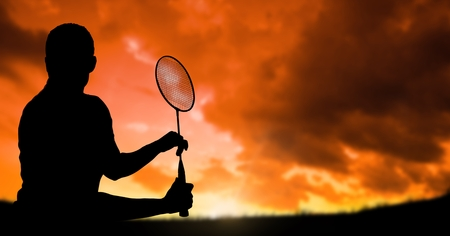 Digital composite of Silhouette man playing badminton against cloudy sky during sunset