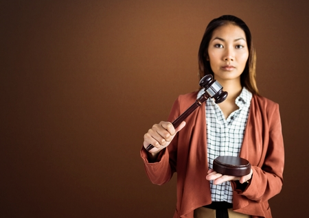 law suit: Digital composite of Judge with balance scale and hammer in front of brown background Stock Photo