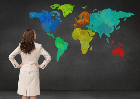 Digital composite of Businesswoman looking at Colorful Map on wall background Stock Photo