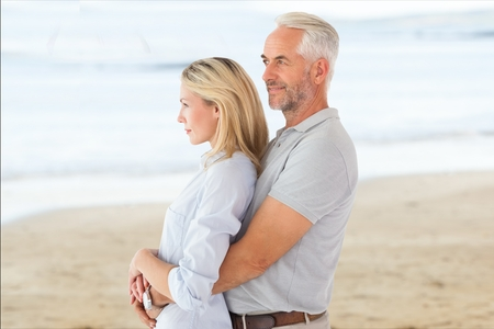 Digital composite of Side view of affectionate senior couple standing at beach Stock Photo