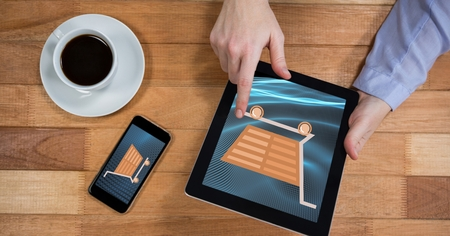 man working out: Digital composite of Hand touching shopping cart icon on tablet PC by mobile phone and coffee cup