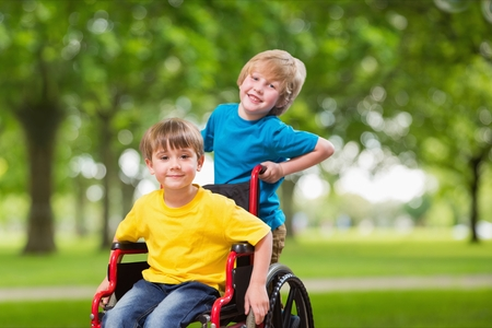 Digital composite of Portrait of boy pushing brother in wheel chair Stock Photo