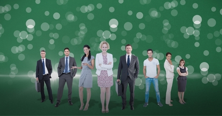 Digital composite of Business people standing against lens flare in green background