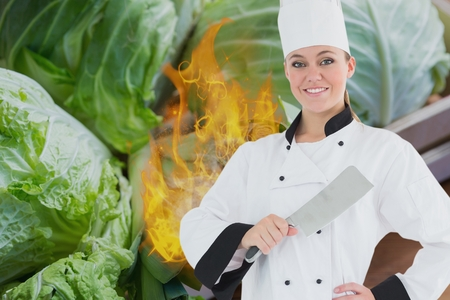 Digital composite of Portrait of chef holding kitchen knife with fire and vegetables in background