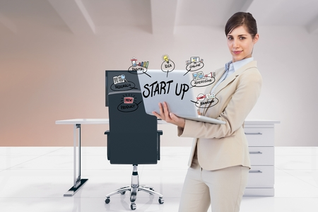 Digital composite of Digital composite image of businesswoman using laptop with start up text and icons in office Stock Photo