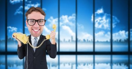 Digital composite of Nerd businessman holding telephone