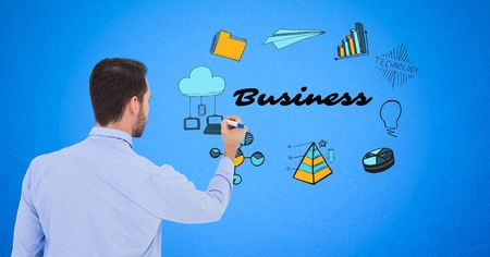 Digital composite of Businessman drawing graphics with business text on screen