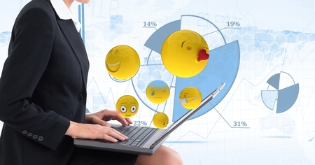 career fair: Digital composite of Digital composite image of emojis flying by businesswoman using laptop against tech graphics in back Stock Photo