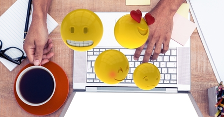 hand holding paper: Digital composite of Digital composite image of emojis flying over hands using laptop at table