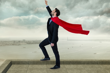 Digital composite of Businessman wearing cape with arm raised  while standing against cloudy sky