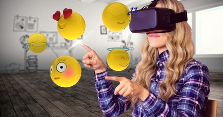 Digital composite of Woman trying to touch emojis while wearing VR glasses