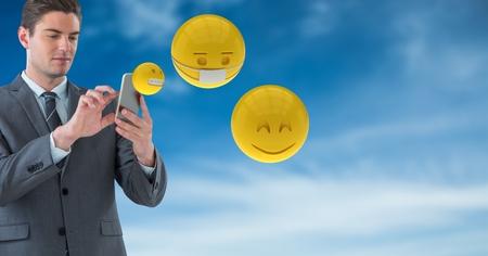 Digital composite of Businessman using smart phones while emojis flying against sky