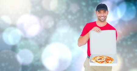 Digital composite of Delivery man showing pizza over bokeh Stock Photo